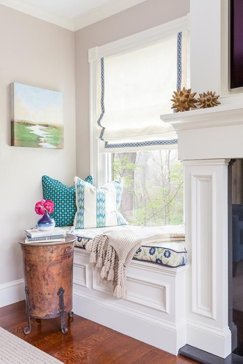 Living room features a flatscreen TV niche over a fireplace flanked by built-in window seats topped with a blue and green country floral cushion with blue piping under window dressed in a white roman shade accented with blue chain link trim alongside a vintage metal accent table.