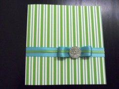 Partecipazione per matrimonio elegante  in carta martellata di qualità con grafica a righe verdi e azzurre. Abbellimenti in nastri di raso negli stessi toni e gioiello decorativo. Misure 15x15cm
