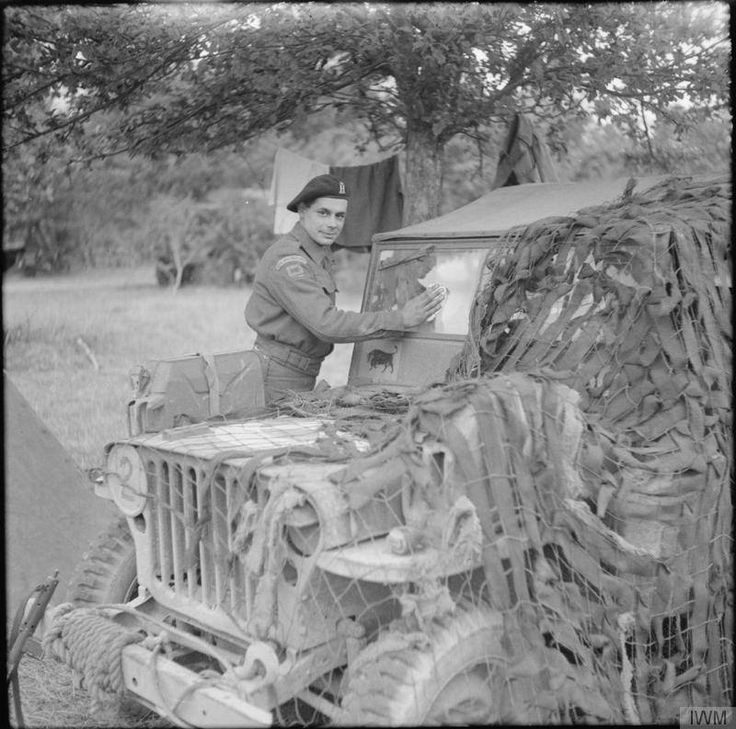 "Trooper M. Fraser, de la Royal Armoured Corps, 11th Armoured Division, nettoye  son jeep Willys MB. Notez le ""taureau rouge cornes 'insigne de la 11e Division blindée."