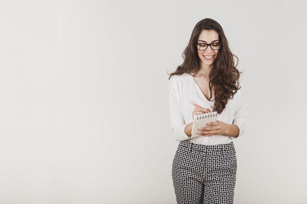 Empresaria atractiva con gafas escribiendo Foto Gratis