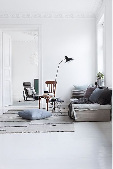 grey decor white walls and flooring throws scatter cushions lamp stand wooden chair high ceilings: