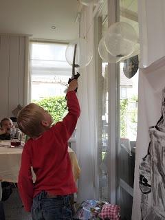 In ons huis: doorzichtige ballonnen ( via Lang zal ze leven) gevuld met confetti en een opgerold briefje met naam van de gast. Zwaard met scherpe punt ( naald eraan) Wie mag als eerste zijn cadeau geven?