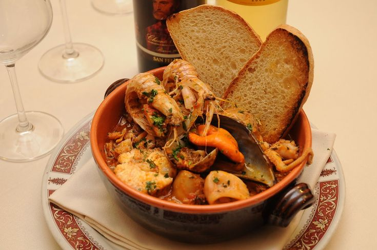 Cacciucco -2-Versate il vino e fate evaporare. Aggiungete i pomodori, fate sobbollire per 10 minuti. Unite i pesci a carne più soda, bagnateli con un po' d'acqua calda, cuocete a fuoco vivo 10 minuti. Aggiungete i pesci più teneri e cuocete 20 minuti. Unite i molluschi. Servite con il pane abbrustolito soffregato con uno spicchio d'aglio.