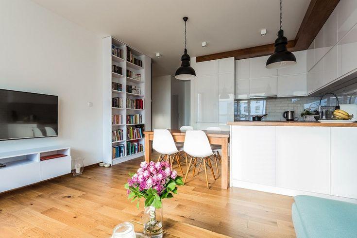 Przestronny salon łączy się z kuchnią oraz jadalnią w jednym pomieszczeniu. Kwiaty w wazonie pełnią funkcję dekoracyjną...