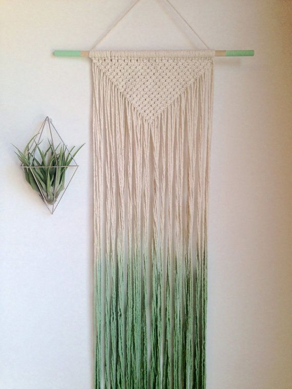 A new, handmade modern macrame wall hanging, dip dyed cotton in mint green, on a wood dowel with painted matching mint green ends.  Approximately 36