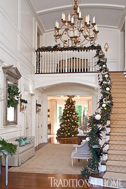 A noble fir is an immediate presence inside this grand entry. Exquisite garland graces the banister. - Traditional Home ®/ Photo: Michael Garland / Design: Emily Sullivan