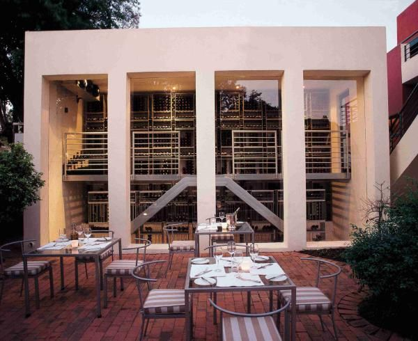The wine cellar provides a decorative backdrop for the outdoor seating at Sides Restaurant