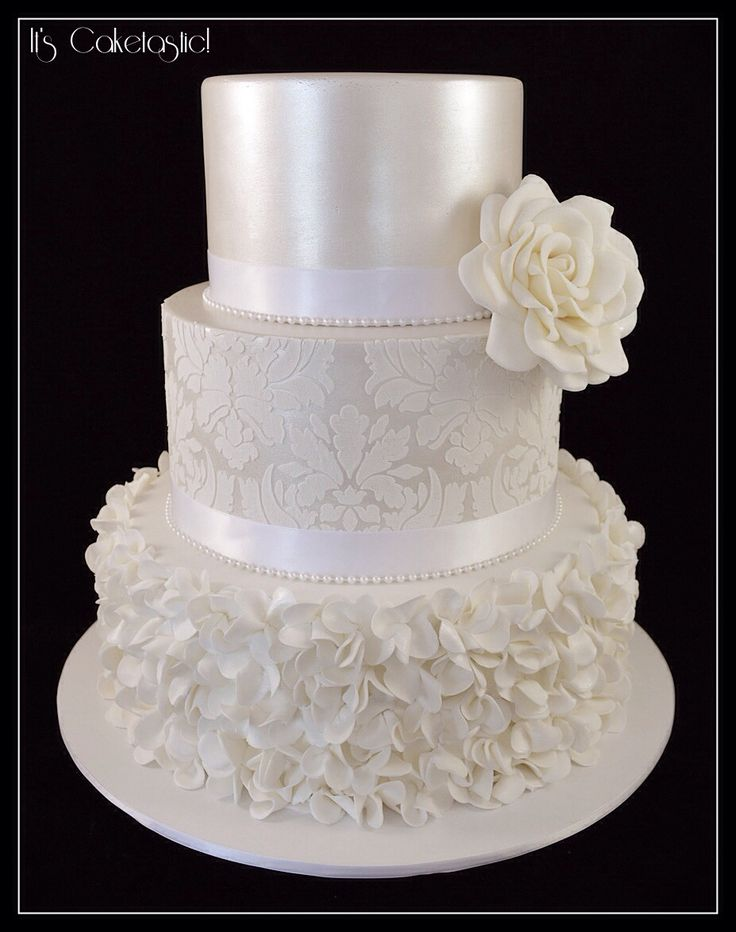 White on white wedding cake - Here's my new favourite wedding cake! The top two tiers were painted with pearl lustre. The damask pattern on the second tier was done with white royal icing so it stood out against the pearl finish. The bottom tier was covered with hundreds of scrunch flowers. I used a six petal cutter and each flower was dusted individually before it was applied to the cake so they shimmered in the light. The happy couple chose red velvet, marble mud and Jaffa mud for their…