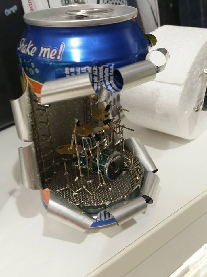 A Miniature Drum Kit Set Up Inside an Empty Can of Orangina