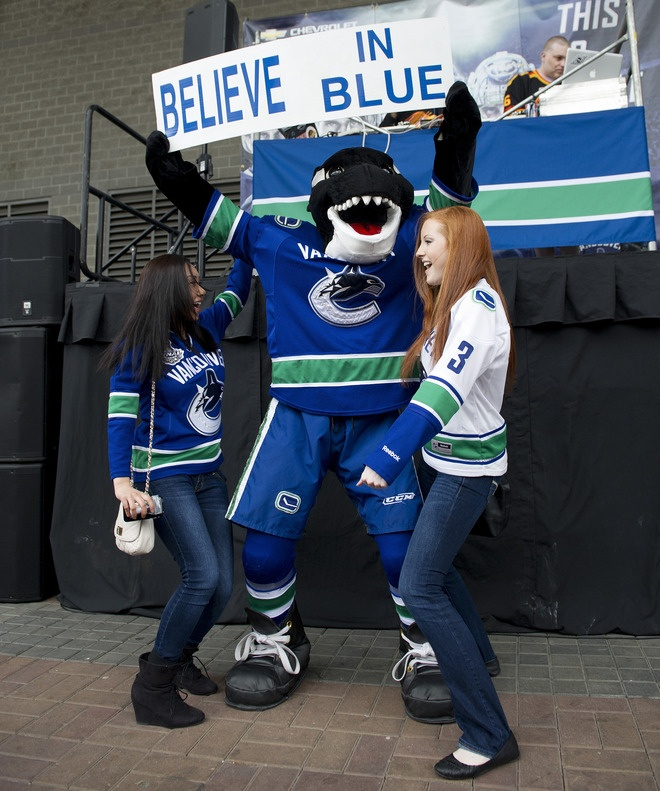 Fans dance with Vancouver Canucks mascot Fin outside outside Rogers Arena