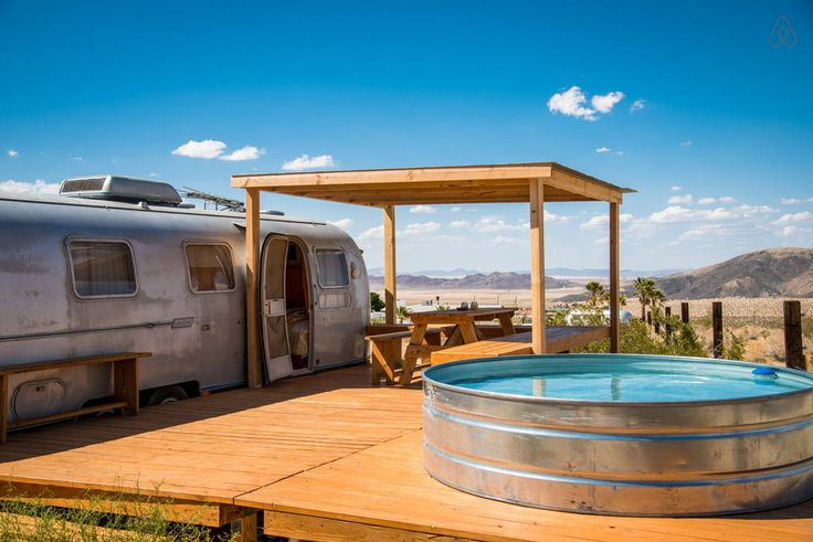 "Camper/RV in Joshua Tree, United States. This is a classic Airstream ""Land Yacht"" travel trailer, that has been converted into a fully functional guest house.  The Land Yacht has its own private deck built alongside it.  The deck also supports a large Stock Tank pool, surrounded by bould..."