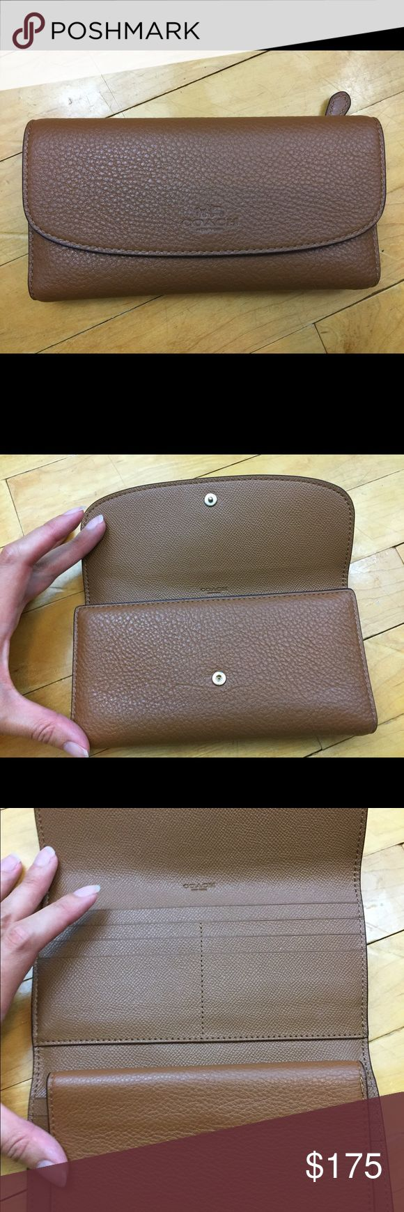 NWT Coach Trifold Wallet NWT Coach Trifold Wallet. This Wallet was made for the factory outlet store. It's made of pebble brown leather. It features 12 cc slots, 2 large pockets and a checkbook cover. It also has a back zipper pocket. Coach Bags Wallets