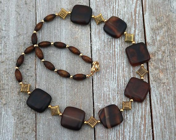 Lovely matte banded onyx is featured in the design of this womans brown necklace. Complimenting the onyx beads are horn beads and gold plated beads. This short necklace is approximately 19 inches long and features a gold plated lobster claw clasp. This stunning necklace will make #longbeadednecklace