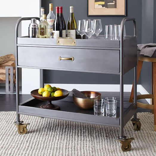 NEW! The Workshop Bar Cart is made from a blackened metal frame and features brass-finished detailing. A drawer and two open shelves at the top and bottom are great for additional storage and displaying your favorite vintages.