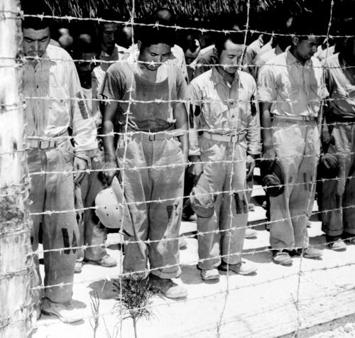 Japanese POW's located on the island of Guam, bow their heads after hearing Emperor Hirohito announce on the radio—for the first time in the history of Japan and Hirohito's reign—of the unconditional surrender of all Japanese forces in the Pacific..