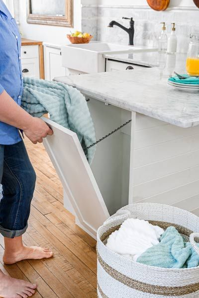 A faux cabinet door on the end of this kitchen's peninsula conceals a new laundry chute, which directs dirty linens straight to the basement laundry room. | Photo: Andrea Rugg | thisoldhouse.com