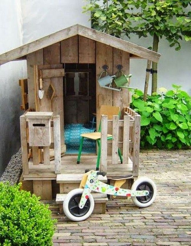 Building a wooden pallet cabin or playhouse beside your garden to hang the tools there or sit peacefully is not that difficult. Try not to make it too big but make it spacious. You can put a hut roof and make a little boundary around. You can also put your kid's cycle there.