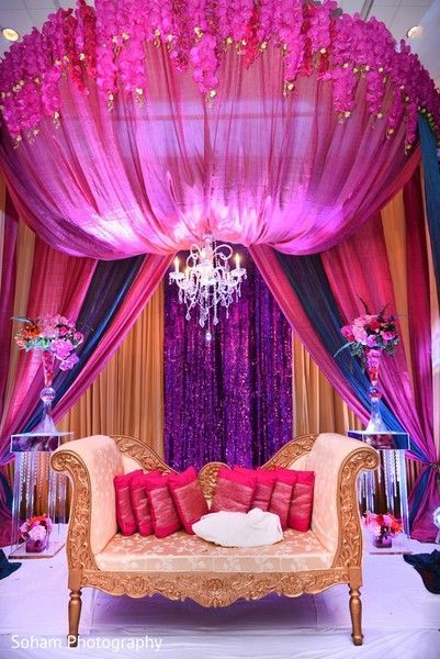 pink purple blue and gold reception backdrop with a chandelier