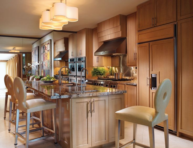 Barstools from Artistic Frame covered in F. Schumacher's sandy-hued raffia pull up to this kitchen island, illuminated overhead by Hinson & Co.'s swirling pendants from Jerry Pair. Warm-toned, faux zebra-striped maple-wood cabinetry and granite countertops add a sophisticated tone.