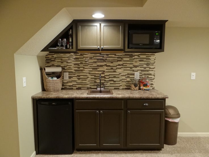Basement wet bar under stairs used stock cabinets and for Basement cabinet ideas