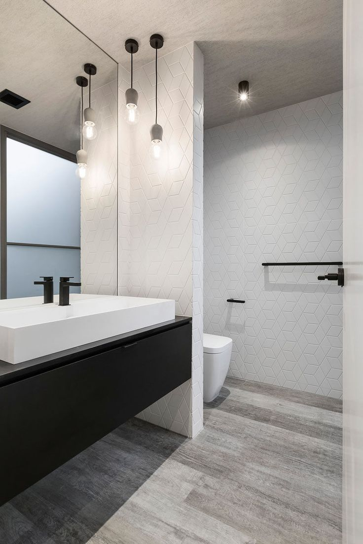 This mostly white bathroom with a black vanity, has simple pendant lights hanging in the corner.