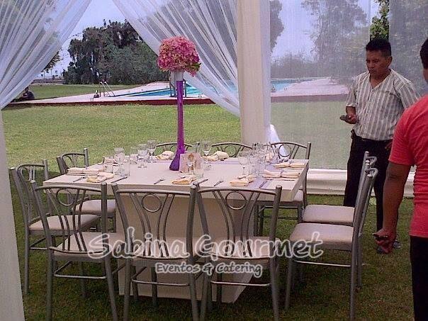 Mesa con sillas tiffany para los invitados y decoración con flores naturales