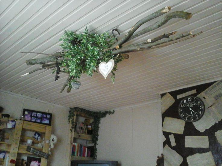 Een oude kroonluchter ontmanteld, takken uit het bos,  en wat vals groen vormen mijn nieuwe verlichting in de woonkamer