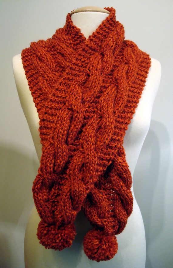 Handmade knitted orange scarf with cables and pom poms