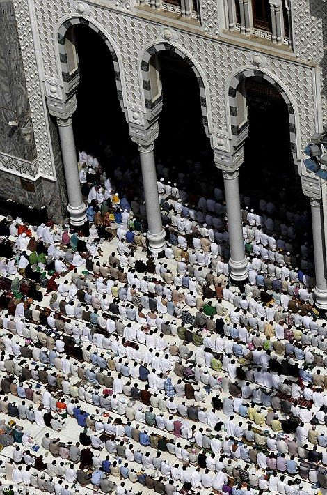 Muslim pilgrims pray outside the Grand mosque in Mecca, Saudi Arabia, Monday, Oct. 22, 2012.
