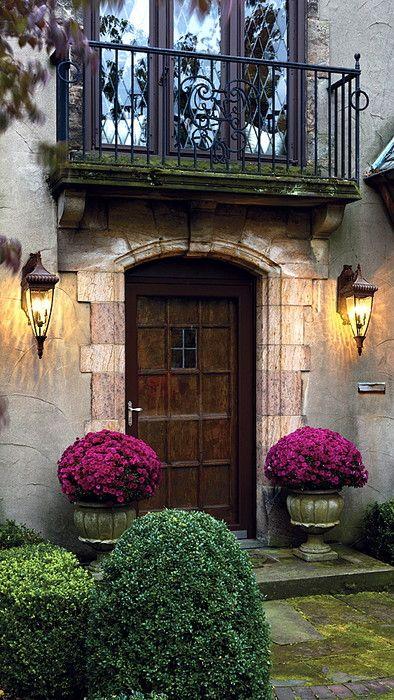 Porta de madeira ladeada por vasos floridos e acima balcão de ferro forjado.