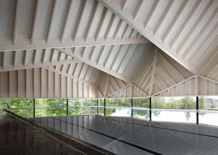 A folded timber roof adds drama to the interior of this school swimming pool.