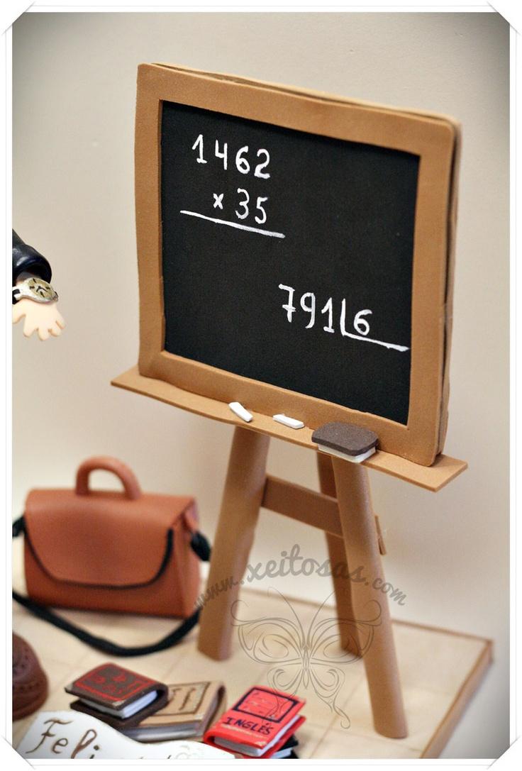 Fofucha Profesora con pizarra y libros. Todos los detalles son personalizados, la ropa, reloj, foulard, calzado, maletín...y todo en goma eva. www.xeitosas.com/