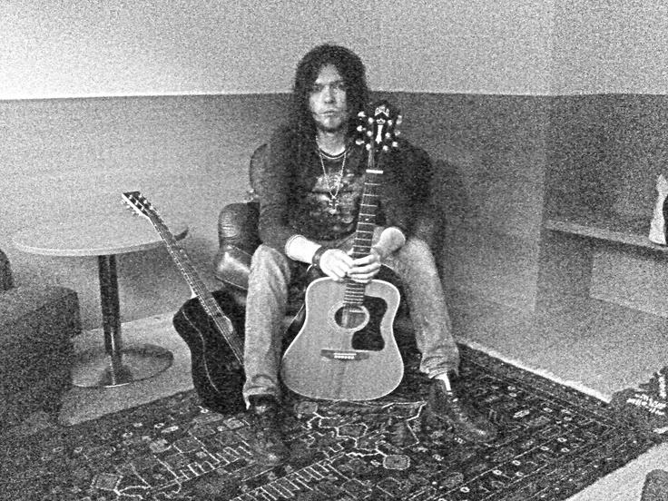 black and white of Hannu w/ one of his acoustic guitars
