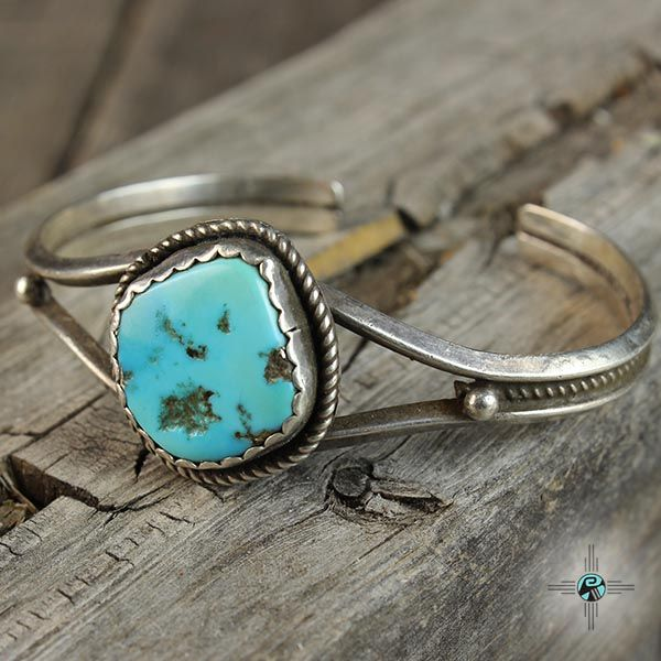 This is a simple vintage Navajo turquoise bracelet. The piece is centered with a lovely natural turquoise stone measuring 3/4″ in diameter. The stone rests on a sturdy three shank silver cuff. The piece is old but in great condition. Cir. 1980's. The bracelet is Sterling Silver and made by an Unknown Navajo artist. The bracelet cuff measures 5-3/4″ with a 1″ gap for a wrist measuring around 6-3/4″. The piece is 1″ at its widest point.