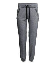 Sports sweatpants with an elasticized drawstring waistband, side pockets with zip, and elasticized hems.