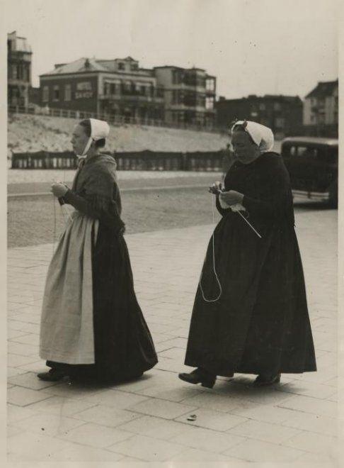Scheveningse vrouwen wandelen al breiend over de Boulevard; de linker vrouw draagt een nachtmuts met gekleurde doek en bont schort, de rechter vrouw draagt rouwkleding; op de achtergrond Hotel Savoy aan de Zeekant. ca 1935 Polygoon #ZuidHolland #Scheveningen