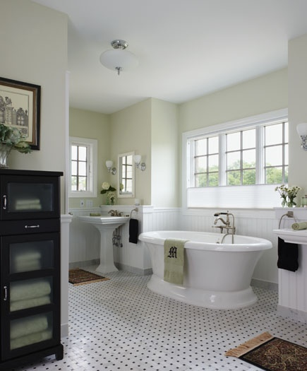 Traditional black and white marble floors accent this Old English bathroom appointed with modern amenities.