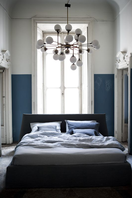 A great treatment of a long thin tall bedroom space with blue walls painted half way up the wall to make it cosier and a fabulous mid century chandelier making use of the tall eaves. Studiopepe—Ivano Redaelli