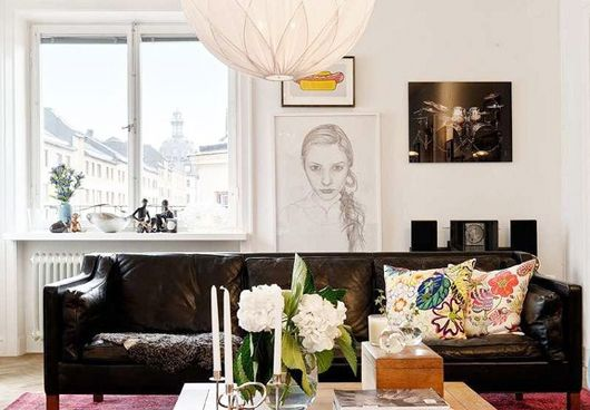 black-leather-softened by bright cushions, flowers, and a lovely illustration