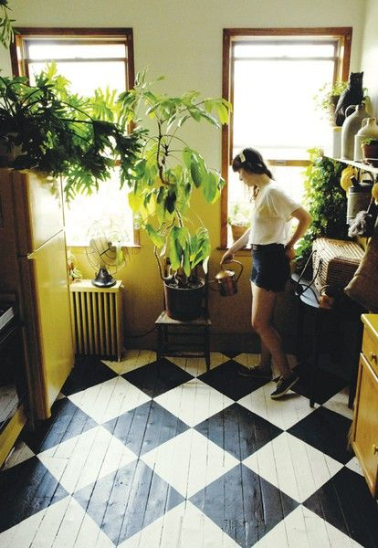 Black and white floor painted with an oversize diamond pattern and teamed with huge house plants.