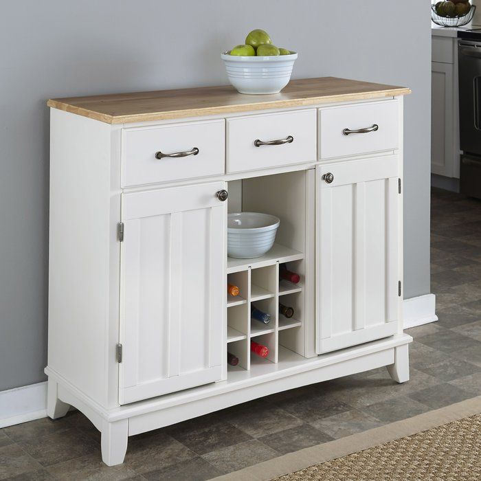Whether you're completing your well-stocked kitchen or adding a simple storage solution to your low-key living room ensemble, this understated server brings a perfect balance of subtle style and effortless utility to your ensemble. Set it against an off-white or gray wall to complement its oak-finished top, then top it off with a bowl of faux fruit or pinecones to tie a farmhouse-inspired twist into the look. Featuring three top drawers and two side cabinets, this design offers ample spac...