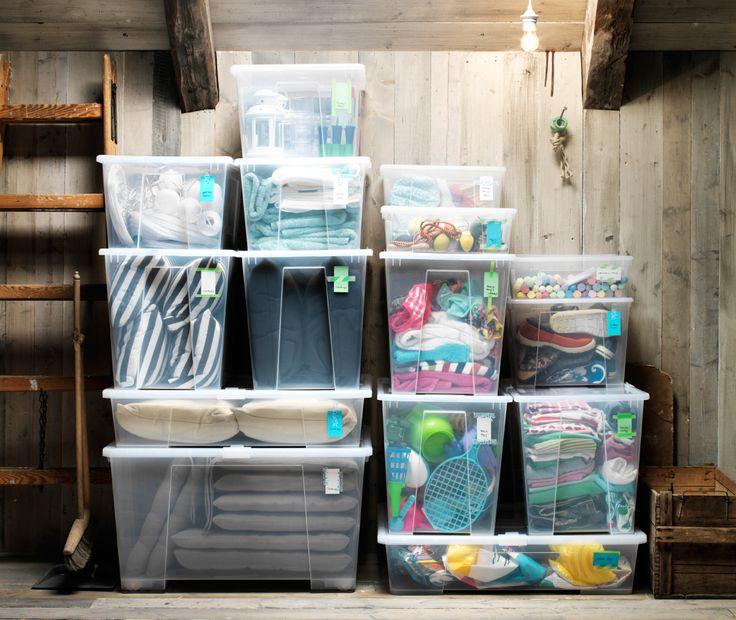 See-through storage boxes filled with clothing and toys piled up in an orderly manner against an attic wall.