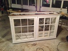 Two old windows framed in with veneered oak plywood. Painted brown, then black and then primed for the top coat. Two pieces of oak married together to form the top stained with a dark walnut...