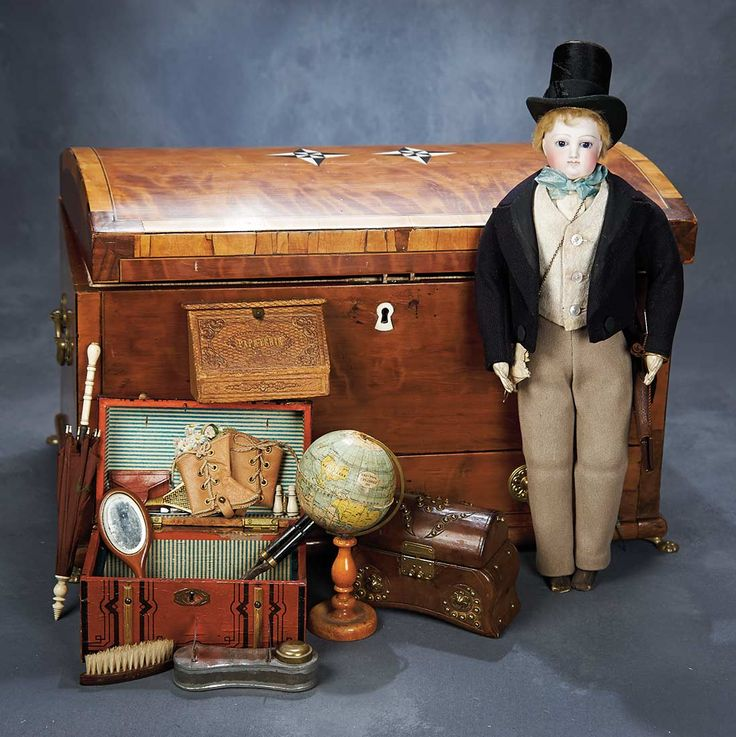 """Theriault's Antique Doll Auctions - French Bisque Gentleman Poupee with Wooden Trunk and Many Accessories - 16"""" -  French, circa 1865. The gentleman wears his original woolen suit with silk brocade vest, leather boots & wonderful top hat.  Leather folio dated 1864. He is presented in his finely-crafted wooden trunk with silk lining, dove-tailed construction and brass claw feet. The trunk contains a variety of gentleman's accessories."""