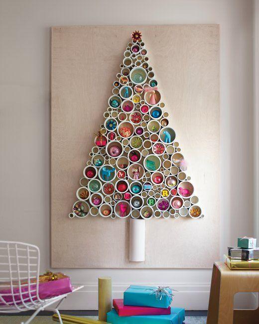 Árbol de Navidad creado con recortes de tuberias de PCV de diferentes diamentros, que una vez pintados se pegan sobre un tablero. En los huecos de cada cilindro se decora con figuras y bolas de Navidad. Muy original y divertido.