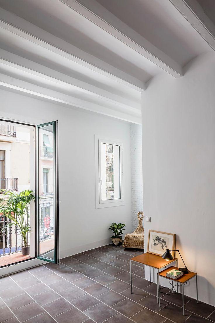 Sala de estar reformada, piso cinza escuro original, paredes brancas, ambiente minimalista. Apartamento Minimalista em Barcelona por RAS Studio
