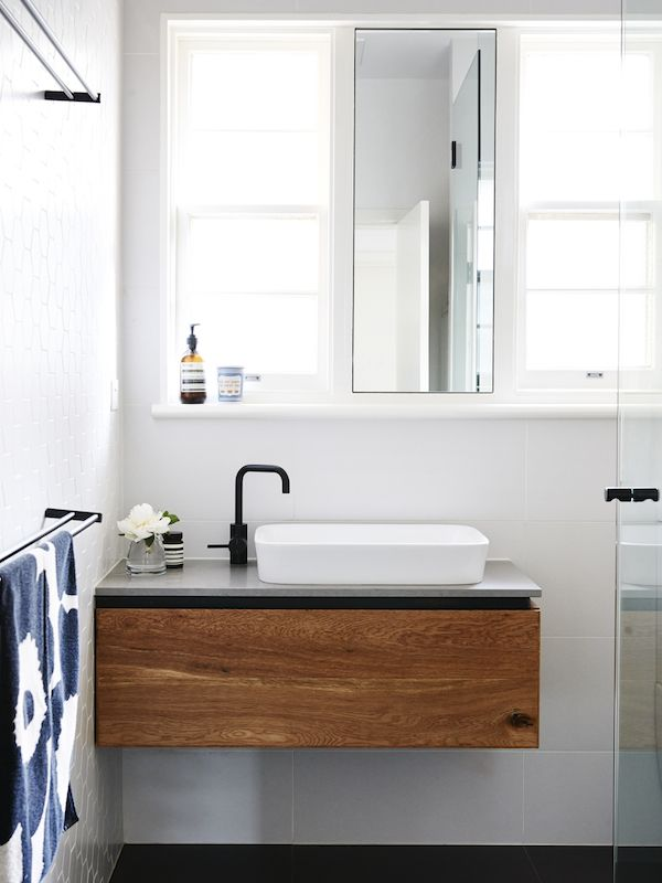 Bathroom. Marimekko towel, Iconic New York 'We are happy to serve you' ceramic cup from MOMA, NYC. Custom designed oak and black steel vani...