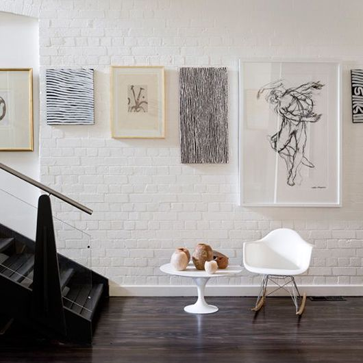 An art collection on a white painted brick wall, aligned along the top of the frames.