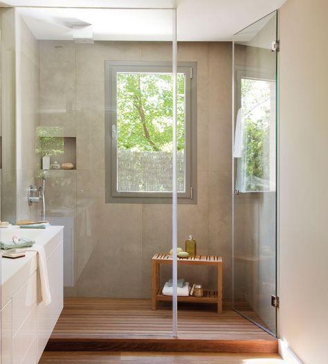 Baño con gran gran ducha a medida, ventana y tarima de madera en la ducha