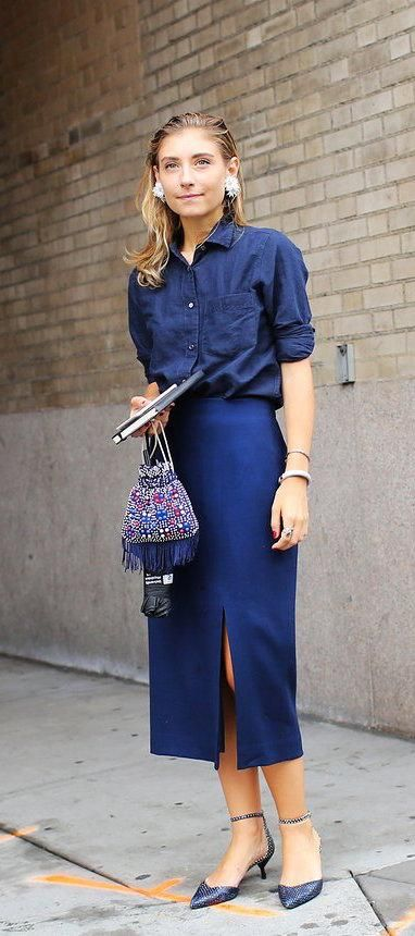Jenny Walton in a blue button down and slit skirt